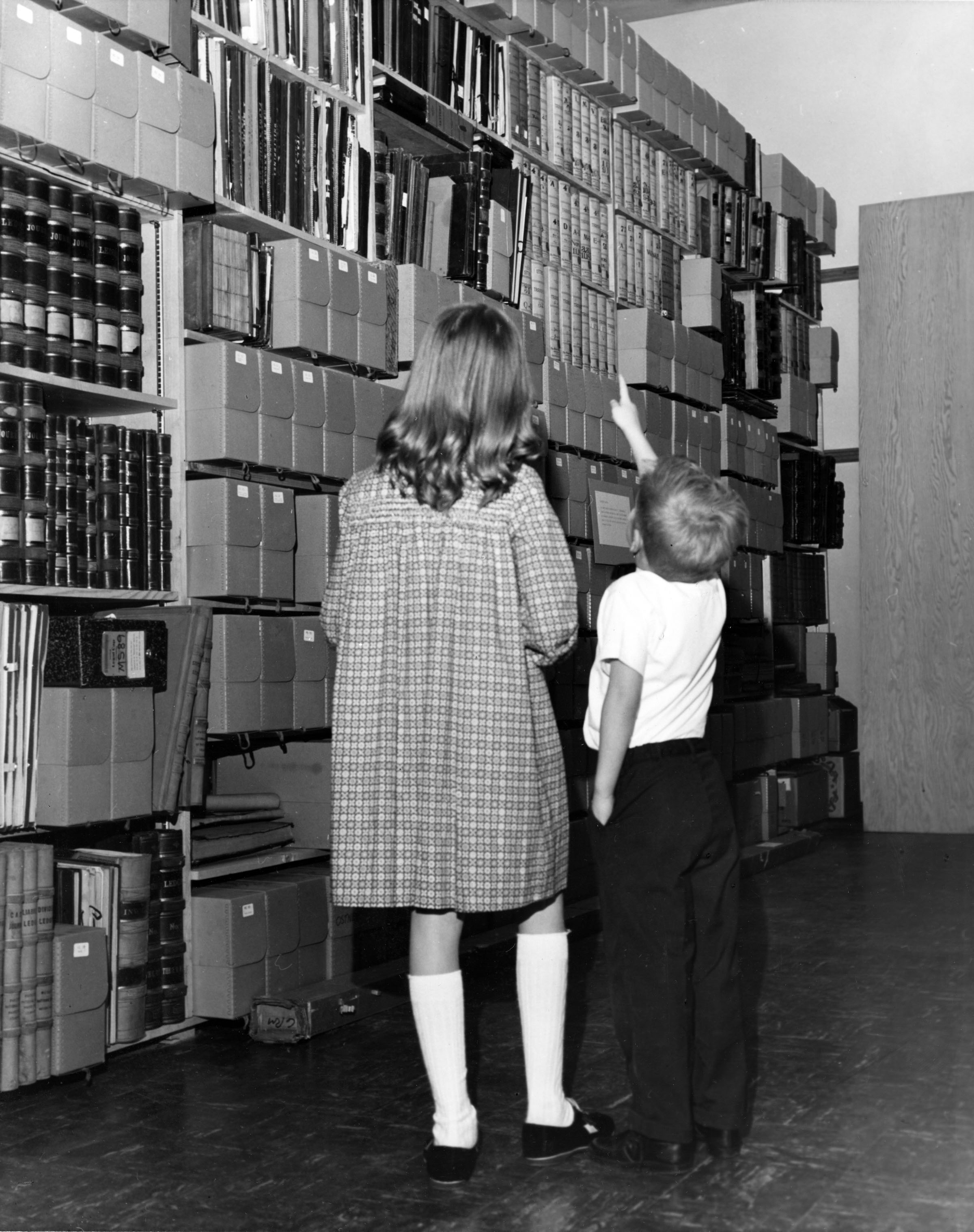 Two children looking at archival shelves